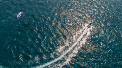 People are playing parachute at sea during summer holidays. Aerial view.