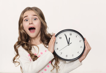 Excited little girl with clock at white background