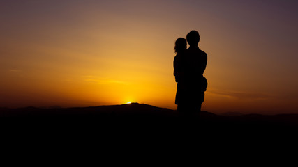Couple woman man hugs tightly at colorful beautiful sunset with horizon in the background - concept love young romance embrance nature silhouette for ever marriage people old mood feelings holiday
