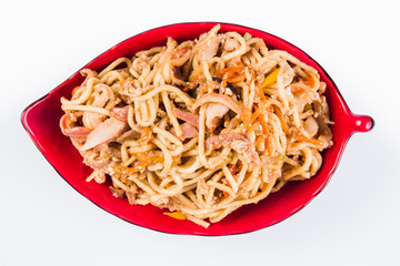noodles with bacon and pepper on a red plate on a white background. Traditional Italian pasta. Close top view