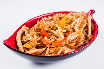 Thick glass noodles with chicken pepper and sesame seeds on a red plate on a white background. Traditional Italian pasta. Close