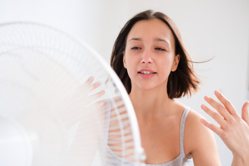 Woman refreshing in front of a electric fan ventilator