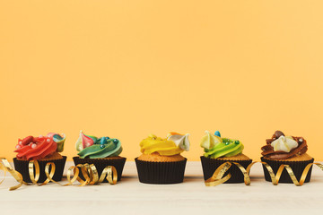 Chocolate cupcakes in a row with colourful icing