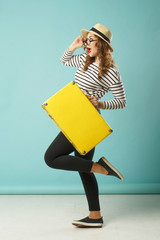 Young happy beautiful woman in hat and funny toy glasses holding yellow suitcase