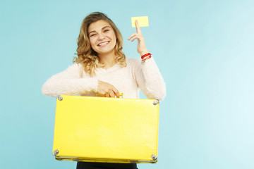 Young happy woman holding empty credit card in one hand and yellow suitcase in another over blue background