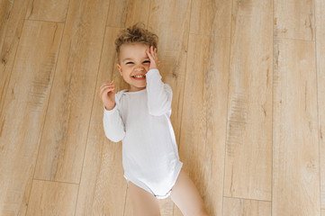 overhead view of cute little smiling boy in white bodysuit lying on floor at home