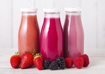 Glass bottle with fresh summer berries smoothie