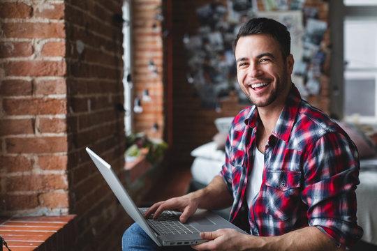 Cheerful man using computer at home.