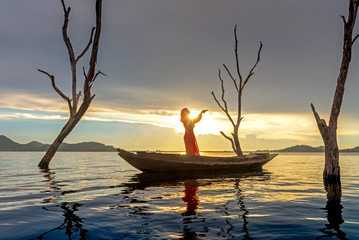 Veiled Islamic muslim woman wearing a burka standing and praying on the boat in the sunset.