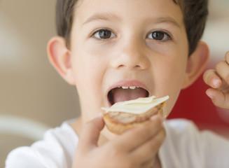 Niño comiendo montadito de queso