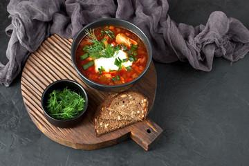 Borsch,  beetroot soup in ceramic  bowl  on dark background, traditional dish of ukrainian cuisine