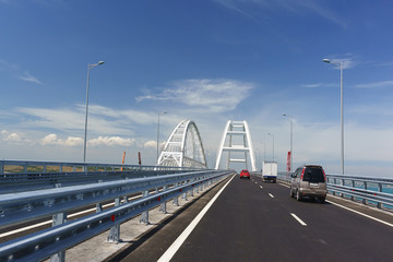 Cars on the Crimean bridge drive up to the white metal arches over the fairway
