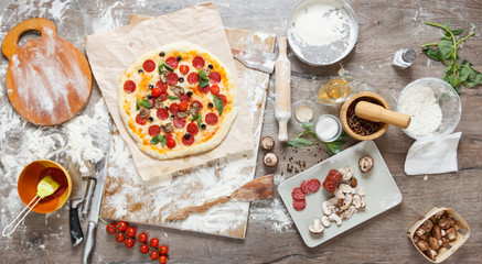 Top view cooking pizza with ingredients, tomatoes, salami and mushrooms on wooden tabletop