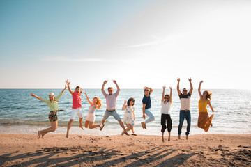group of happy young people jumping at the beach on beautiful summer sunset. Nine person, five women and four men. Friends and holiday concept