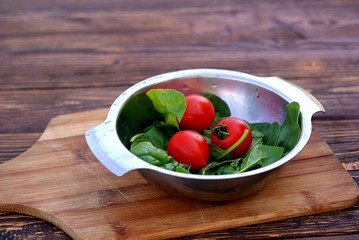 Ripe tomatoes and fresh spinach leaves in a metal bowl on a wooden background. Healthy food concept.