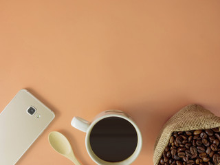 Flat lay a cup of coffee and smartphone on desk with copy space