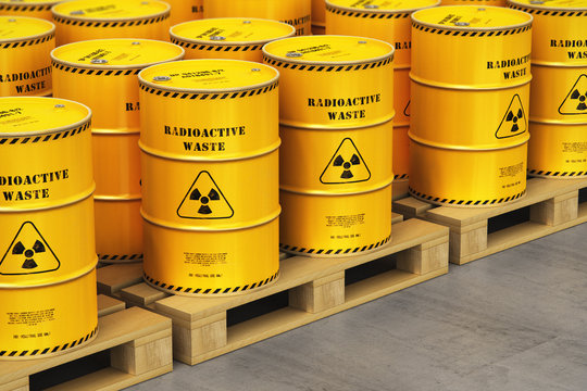 Group of yellow drums with radioactive waste on shipping pallets in warehouse