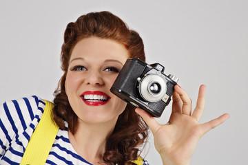 femme pin-up rousse avec appareil photo vintage
