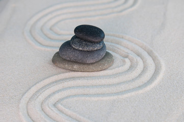 Photo sur Plexiglas Zen pierres a sable Pyramids of gray zen stones on light sand. Concept of harmony, balance and meditation, spa, massage, relax