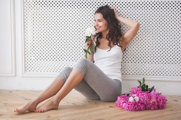 Very beautiful young woman with flowers. Portrait of attractive girl with peonies