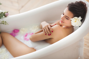 Young attractive woman taking bath with milk and flowers