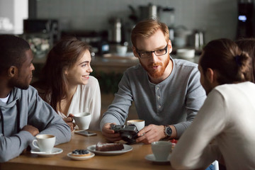 Young redhead guy holding camera showing photos sharing recent memories or travel impression hanging with diverse friends, smiling multiracial millennial people talking sitting together at cafe table