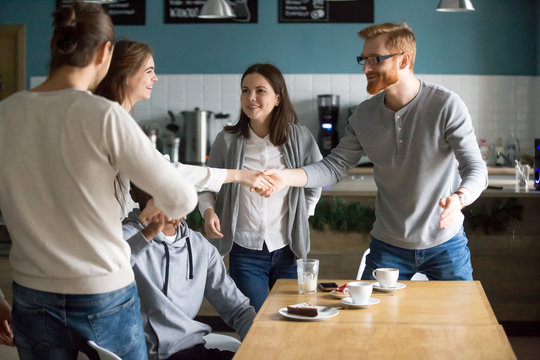 Millennial guy handshaking smiling girl introducing greeting at group meeting in cafe, happy young people get acquainted hanging together at public place, making new friends, first impression concept