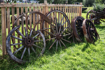 Old and broken wagon wheels against a fence