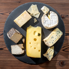top view of tasty various types of cheese on slate stone background
