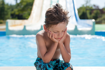 sad lonely little boy sitting near water pool in summer resort water park