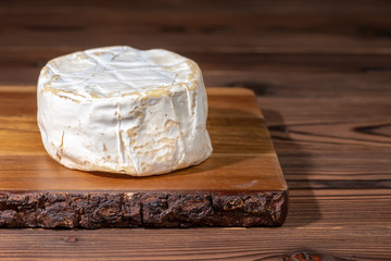 whole white cheese with mold on wooden background