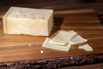 portion and slaced of fresh parmesan cheese on wooden table
