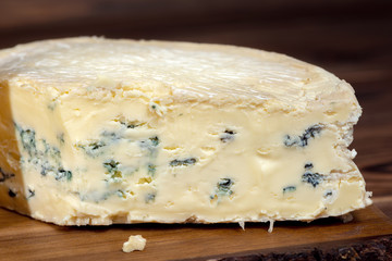 tasty whole blue cheese with mold on wooden background, close up, Italian, French cheese