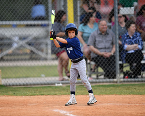 Young Boy batting during a Little League baseball game