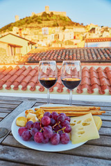 Red wine with delicious cheese, bread and grapes