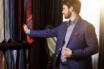 Elegant European Man choosing necktie or tie to match his suit in custome made garment fashion boutique