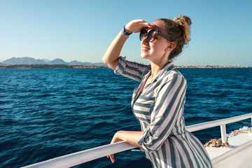 pretty girl with sunglasses happy looking forward  while travels on yacht