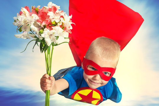 A child in a superhero costume with a bouquet of flowers flies to her beloved mother.