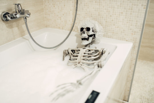 Scary human skeleton lying in the bathtub, humor