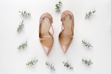 Bridal shoes with oregano branches on white marble. Top view.