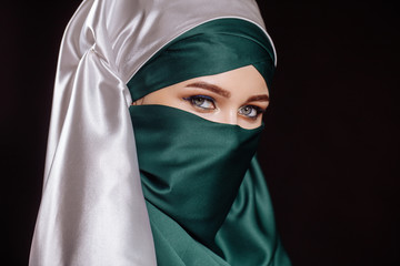close up side view portrait of pleasant Arab woman covering her head with scarf isolated on the black background