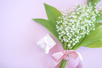 Tuinposter Lelietje van dalen Pink gift box with engagement ring and bouquet of lilies of the valley on pink background with copy space