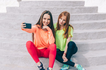 Two girl friends in sporty outfits do a joint selfie