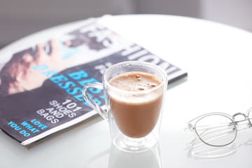Cup of aromatic coffee and magazine on table