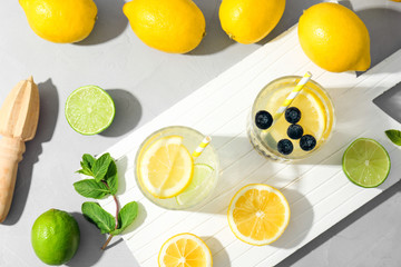 Flat lay composition with delicious natural lemonade on light background