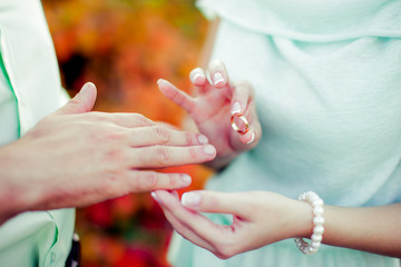 wedding ceremony puts a ring on the finger of the groom and the bride offering an engagement happy moment