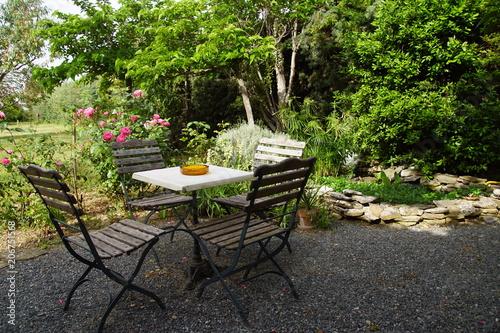 Table et chaise sur terrasse ombragée et bassin d\'agrément\