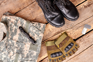 Flat lay, set of military camouflage outfit. Top view, Wooden background.