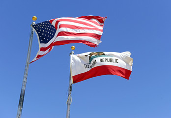 California state flag and American flag with blue sky background, waving in the wind
