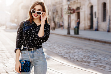Outdoor portrait of yong beautiful happy smiling woman wearing stylish sunglasses, black polka dot blouse, blue mom jeans, with small quilted bag. Model posin in street of european city. Copy space